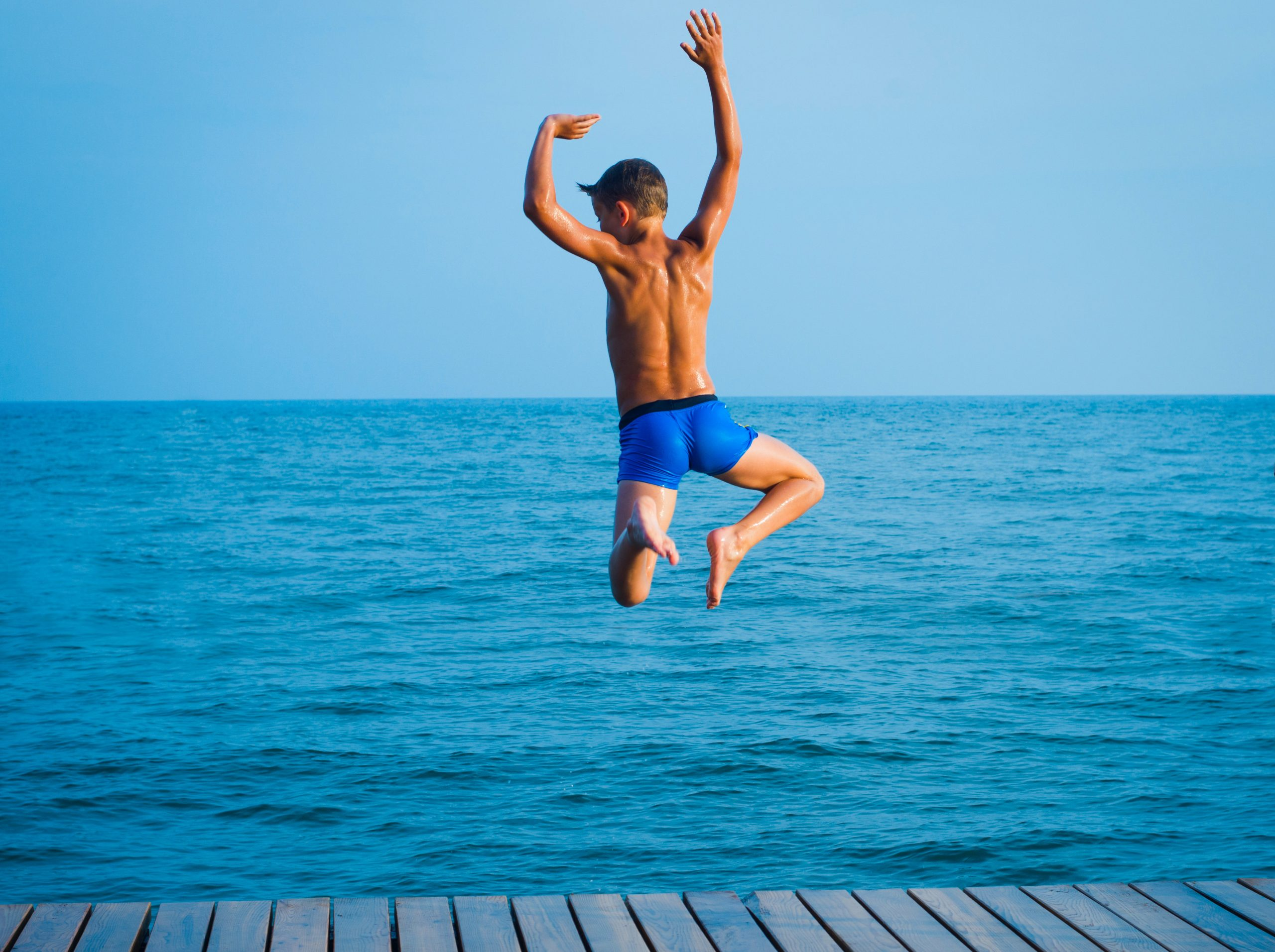 Niño saltando playa
